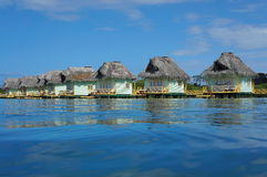 Karibische Meere über Wasserbungalows mit Strohdach Stockfotografie