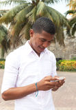 Karibischer Kerl, der eine Textnachricht schreibt Stockfotografie