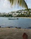 Karibischer sandiger Strand mit BootsPalme Stockfotos