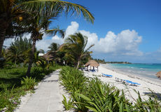 Karibischer weißer Sandstrand und landschaftlich gestalteter Bürgersteig an einem tropischen Erholungsort Lizenzfreie Stockfotos