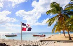 Karibisk strand och Dominikanska republikenflagga Arkivbild