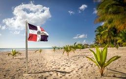 Karibisk strand och Dominikanska republikenflagga Royaltyfria Foton