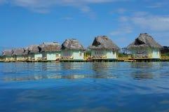 Karibiska over vattenbungalower med det halmtäckte taket Arkivbild