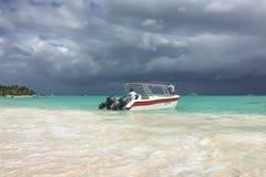 Karibiskt hav för regnet Fartyg med två personer som förtöjas på kusten Moln s?tta p? land fin white f?r sandturkosvatten royaltyfria bilder
