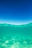 Karibiskt hav för klar vattenlinje som är undervattens- och över med blå himmel Royaltyfria Bilder
