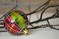 Karierter Weihnachtsball und -zweige Lizenzfreies Stockfoto