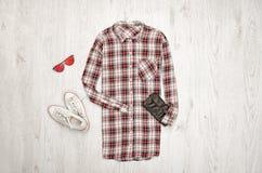 Kariertes weibliches Hemd, schwarze Handtasche, weiße Turnschuhe, Gläser Modernes Konzept, hölzerner Hintergrund Lizenzfreies Stockbild