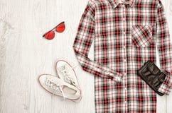 Kariertes weibliches Hemd, schwarze Handtasche, weiße Turnschuhe, Gläser Modernes Konzept, hölzerner Hintergrund Lizenzfreie Stockbilder