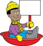 Karikatur-Afroamerikanerjunge, der in einem Schlitten sitzt und ein Zeichen hält Stockbild