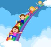 Karikatur-Kinder, die hinunter einen Regenbogen schieben Stockfoto