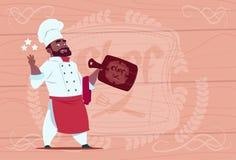 Karikatur-Restaurant-Leiter Afroamerikaner-Chef-Koch-Hold Star Awards lächelnder in der weißen Uniform über hölzernem strukturier Stockfotografie