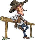 Karikaturcowboy, der auf einem Zaun sich lehnt Stockfoto
