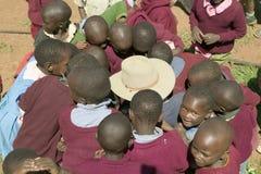 Karimba School with school children surrounding white man with straw hat on, in North Kenya, Africa Royalty Free Stock Photo