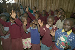 Karimba szkoła z dziecko w wieku szkolnym podnosi ich ręki w sala lekcyjnej w Północnym Kenja, Afryka Zdjęcie Stock