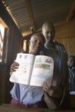 Karimba szkoła z dziecko w wieku szkolnym trzyma up ich podręcznika w sala lekcyjnej w Północnym Kenja, Afryka Zdjęcia Stock