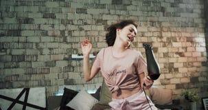 Karismatisk dam i pyjamas som får klar i morgonen genom att använda en hårtork för att få ett nytt och torrt hår i hennes säng in stock video