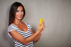 Karismatisk hållande mobiltelefon för ung dam Fotografering för Bildbyråer