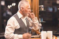 Karismatisk klient som undersöker hans utseende, når att ha fått frisyr i frisersalong Arkivfoton