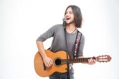 Karismatisk positiv ung man som sjunger i mikrofon och spelar gitarren Arkivfoton