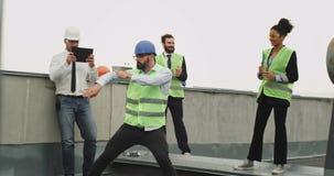 Karismatisk tekniker med en skäggdans på avbrottstiden framme av hans kollegor på taket av konstruktion stock video