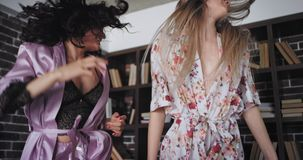 Karismatiska två damer i nätt pyjamas i morgonen har stort hoppa för lynne spännande över säng i ett modernt sovrum stock video