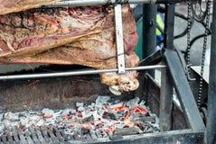 Karkassen van varkensvlees en ander die vlees op vleespen wordt voorbereid Het koken op grill en brand royalty-vrije stock afbeeldingen