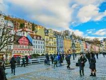 Karlovy varierar, den Cszech republiken - Januari 01, 2018: Folket som går på mitten med fasader av gamla hus Royaltyfri Foto