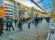 Karlovy varierar, den Cszech republiken - Januari 01, 2018: Folket som går på mitten med fasader av gamla hus Royaltyfria Bilder