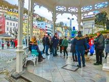 Karlovy varierar, den Cszech republiken - Januari 01, 2018: Folket som går på mitten med fasader av gamla hus Arkivfoto