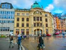 Karlovy varierar, den Cszech republiken - Januari 01, 2018: Folket som går på mitten med fasader av gamla hus Royaltyfri Fotografi