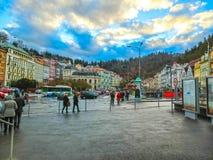 Karlovy varierar, den Cszech republiken - Januari 01, 2018: Folket som går på mitten med fasader av gamla hus Arkivbilder
