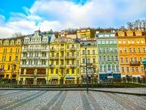 Karlovy varierar, den Cszech republiken - Januari 01, 2018: Folket som går på mitten med fasader av gamla hus Fotografering för Bildbyråer