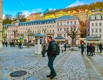 Karlovy varierar, den Cszech republiken - Januari 01, 2018: Folket som går på mitten med fasader av gamla hus Royaltyfri Bild