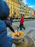Karlovy varierar, den Cszech republiken - Januari 01, 2018: Mandrinkvattnet från en varm termisk vår i Karlovy varierar, tjecken Royaltyfri Foto