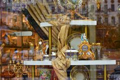 Store. Shop window with different objects. Karlovy Vary, Czech Republic, October 2017: Store. Shop window with golden hours, candlestick, with glasses, cups and stock images