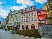 Karlovy Zmienia, Cszech republika - Styczeń 01, 2018: Ludzie iść przy centrum z fasadami starzy domy Fotografia Royalty Free