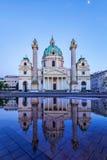 Karlskirche en Viena Austria en la puesta del sol con la reflexión fotografía de archivo