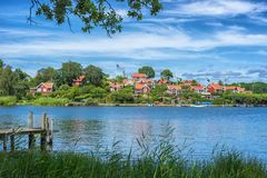 KARLSKRONA, SWEDEN - 2017 July. Typical red Swedish wooden houses with natiaonal flag in the city of Karlskrona Royalty Free Stock Photography