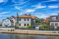 KARLSKRONA, SWEDEN - 2017 July. Typical red Swedish wooden houses with natiaonal flag in the city of Karlskrona Stock Photos