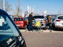 Family shopping for food in Kaufland supermarket parking stock photography