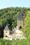 Karlstejn Castle. A large Gothic Castle in southwest of Prague among green trees on hill and blue sky behind. One of the most famous and most frequently visited Stock Image