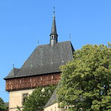 Karlstejn Castle. Part of Karlstejn Castle with wooden wall a large Gothic Castle in southwest of Prague with blue sky behind and trees around. One of the most Stock Photo