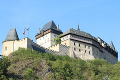 Karlstejn Castle. Side view of Karlstejn Castle on the hill, a large Gothic Castle in southwest of Prague, with green bushes around and blue sky behind Royalty Free Stock Photo