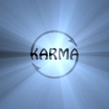 Karma letter Buddhism sign light flare. Isolated Karma symbol with cycling arrows meaning cause and effect, action reaction, causality theory, what comes around Royalty Free Stock Photos