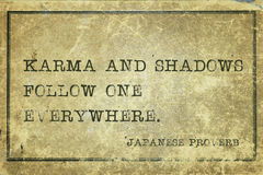 Karma and shadows JP. Karma and shadows follow one everywhere - ancient Japanese proverb printed on grunge vintage cardboard Royalty Free Stock Photo