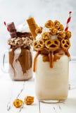 Karmel i czekoladowi szaleni freakshake milkshakes z brezel goframi, popkornem, marshmallow, lody i batożącą śmietanką, Zdjęcie Royalty Free