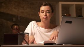 Karmiąca up caucasian kobieta siedzi przy pracującym biurkiem z zanudzającym spojrzeniem i używa laptop salowego
