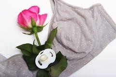Karmiący stanik dla matek i anatomically kształtny płaski pacyfikator dla nowonarodzonego Rosebud menchie barwi w języku obraz stock