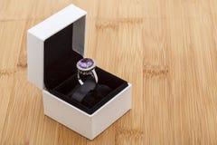 Karminroter Ring in einem weißen Kasten Stockfotos