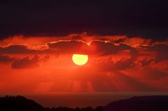 Karminroter Sonnenuntergang über Ozean ~ Sun-Lichtstrahlen Stockfotos